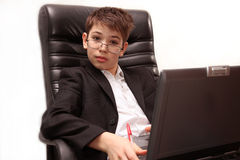 Boy with computer. A boy sitting in large  chair  with a notebook Stock Image
