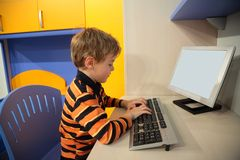 Boy at computer in children's room. Boy at computer in modern children's room Stock Image