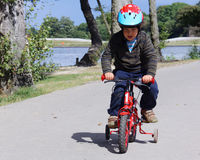Boy Concentrating on Riding Bike with Training Whe Stock Photos