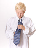 Boy Concentrating on Tying Men's Necktie. Young Blond Boy Pretending to be Grown-Up wearing a man's white dress shirt and blue, striped necktie. Boy is looking Royalty Free Stock Image