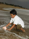 Boy with conch at the sea shore Royalty Free Stock Photography
