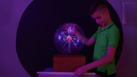Boy conducts electricity and lights the lamp using his body and plasma globe. Tesla globe with electric impulses inside. The museum of popular science and stock video