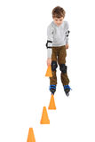 Boy with cone in hand rollerblading near cones Stock Photography