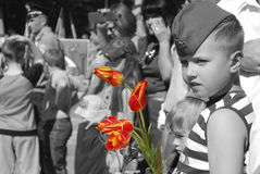 Boy  congratulates veterans on Victory Day and wants to give fl Royalty Free Stock Image
