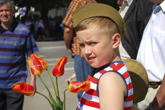Boy congratulates veterans on Victory Day and wants to give flow Stock Images