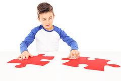 Boy connecting two huge pieces of a puzzle Stock Image