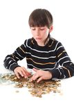 Boy considers money. In piggy bank Stock Images