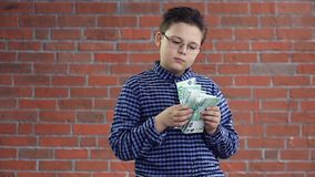 The boy considers money in his hands stock footage