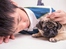 Teen boy and his cute pet pug dog. A teen boy taking care of his pet, an adorable pug puppy with a sad looking face Royalty Free Stock Photo