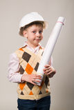 Boy in a construction helmet holding a drawing Stock Photos
