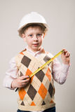 Boy in construction helmet and a tape measure in hand Stock Image
