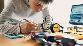 The boy constructs an electronic robot model. Measures the signal in the electrical circuit. Very passionate about work. The boy constructs an electronic robot stock video