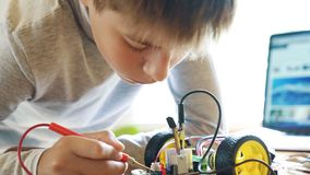 The boy constructs an electronic robot model. Measures the signal in the electrical circuit. Very passionate about work. The boy constructs an electronic robot stock video footage