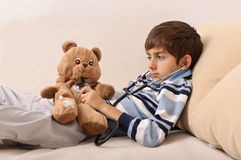 Boy consulting teddy bear Stock Photography