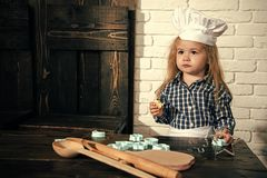 Boy cook in chef hat in kitchen. Homemade cooking and baking. Child using spoon, rolling pin and cookie cutters on table. Playing and learning. Happy childhood Royalty Free Stock Photo