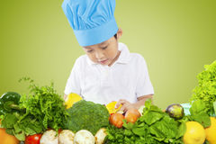 Boy with a cooking hat prepares vegetables Stock Image