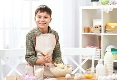 Boy cooking at home, making dough, buns and cookies stock image