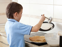 Boy cooking pancakes Stock Images