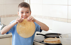 Boy cooking pancakes Royalty Free Stock Images