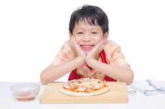 Boy cooking pizza on table Stock Image