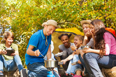 Boy cooks soup in pot for friends at campsite Stock Photo