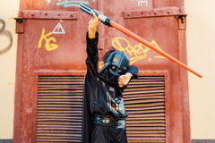 Boy in a costume of  Darth Vader with sword. Royalty Free Stock Photography