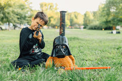Boy in a costume of  Darth Vader and Teddy bear in a mask of Darth Vader with sword. NOVOKUZNETSK, KEMEROVO REGION, RUSSIA - AUGUST 19, 2015 :: Boy in a costume Stock Image