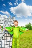 Boy in costume of green dragon near drawn tower Stock Photo