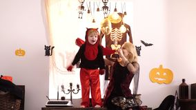 Boy in costume on Halloween party. Little kid in dragon costume with his mother celebrating carnival of Halloween stock footage