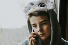 Boy in costume on phone. Young boy in animal costume indoors talking on cell phone Royalty Free Stock Photo