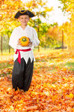 Boy in costume of pirate hold small pumpkin Royalty Free Stock Photos