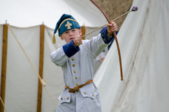 boy in costume shoots toy arrow. A little  boy in 1700 french costume, plays with a bow and toy arrow, at the feast of the strawberry moon festival in grand Stock Photos
