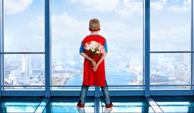 The boy in the costume of a superhero stands with a bouquet of flowers and looks out the window. stock photos