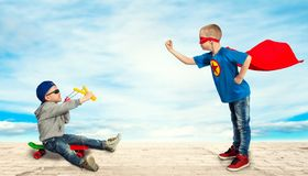A boy in the costume of a superhero, teaches a little bully to the rules of good behavio stock photography