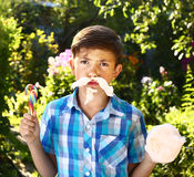 Boy with cotton candy moustache on the summer  background Royalty Free Stock Photo
