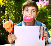 Boy with cotton candy and sheet of paper Royalty Free Stock Photo
