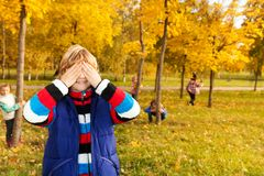 Boy counting while friends hiding. Kids play hide and seek with boy counting covering face with palms while others hiding behind trees Royalty Free Stock Photos