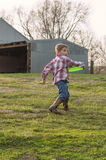 Boy in the country throwing a frisbee Royalty Free Stock Images