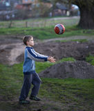 Boy in countryside plays the ball. Boy in the countryside plays the ball in the evening Royalty Free Stock Photos