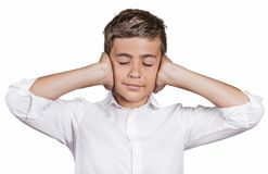 Boy covering ears with hands, doesn't want to hear loud noise, ignoring conversation. Portrait teenager boy covering ears with hands, doesn't want to hear loud Royalty Free Stock Photography
