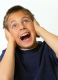 Boy covering ears and yelling Stock Image