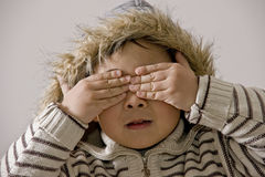 Boy covering eyes. Picture of a little chinese boy covering his eyes with hands for fun Royalty Free Stock Photography