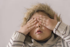 Boy covering eyes. Picture of a little chinese boy covering his eyes with hands for fun Stock Images