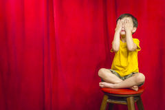 Boy Covering Eyes Sitting on Stool in Front of Red Curtain Stock Photography