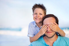 Boy Covering Father's Eyes At Beach Stock Image