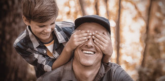 Boy covering fathers eyes in forest Royalty Free Stock Images