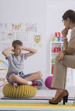 Boy covering his ears. Misbehaved boy covering his ears while talking with psychotherapist Royalty Free Stock Photos