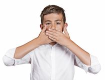 Boy, covering his mouth with hands won't talk. Speak no evil Royalty Free Stock Image
