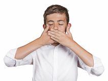 Boy, covering his mouth with hands won't talk. Speak no evil Stock Image