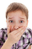 Boy covering his mouth and looking very shocked Stock Photo